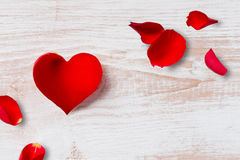 Heart-Shaped Flower Petal and Rose Petals. A red heart-shaped flower petal and rose petals on a wooden surface for Valentine`s Day and other romatic occassions Royalty Free Stock Photo