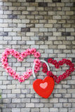 Heart-shaped flowers on a brick wall Stock Photos