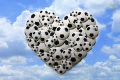 Heart shaped football on blue sky background. A lot of footballs in heart shaped on blue sky background stock photography