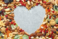 Heart shaped frame of different dried fruits and nuts on color background, top view. Space for text stock photography