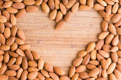 Heart shaped frame of fresh raw almonds. Heart shaped frame of nutritious fresh raw almonds arranged on an old wooden chopping board with central copy space Royalty Free Stock Photography