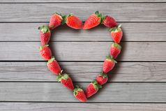 Heart shaped frame made of strawberries royalty free stock photo