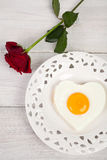 Heart shaped fried egg on beautiful plate with red roses Royalty Free Stock Photo
