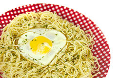 Heart shaped fried egg on pasta Stock Photo
