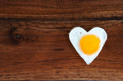 Heart-shaped fried egg on wooden background Stock Images