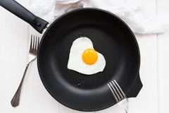 Heart-shaped fried eggs in a black pan. And two forks Royalty Free Stock Photography