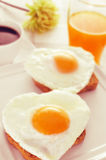 Heart-shaped fried eggs, bread and orange juice Royalty Free Stock Photos