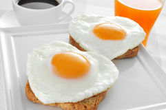 Heart-shaped fried eggs, bread and orange juice Stock Photo