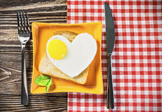 Heart-shaped fried eggs and fried toast Stock Images