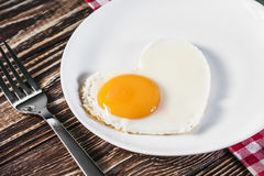 Heart-shaped fried eggs in a plate Stock Photo
