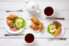 Heart shaped fried eggs, salad, croissants, salami sausage, composition and tea on white wooden table background. Royalty Free Stock Photo