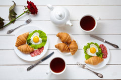 Heart shaped fried eggs, salad, croissants, salami sausage, rose flower composition and tea, white wooden table Stock Image