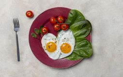 Heart shaped fried eggs with vegetables on plate with fork on white background stock photos