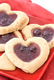Heart Shaped Fruit Filled Cookies on Red Plate. Heart shaped cherry filled cookies on a red plate Royalty Free Stock Photo