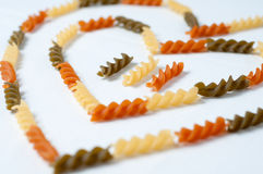 Heart-shaped fusilli pasta. Three colors fusilli raw pasta forming heart shape on white surface Stock Images