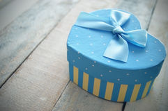 Heart shaped gift box decorated with a blue ribbon Stock Images