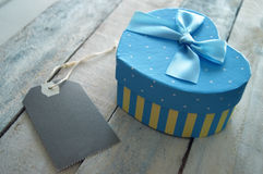 Heart shaped gift box decorated with a blue ribbon and a label Royalty Free Stock Photo