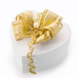 Heart shaped gift box with gold bow. Heart shaped white cardboard gift box tied with an elegant gold bow, braid and pearl for surprising a loved one on Christmas stock illustration