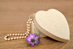 Heart-shaped gift box and pearls. On wooden background royalty free stock photos