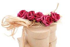 Heart-shaped gift boxes tied with natural raffia and topped with. Some heart-shaped gift boxes tied with natural raffia and topped with artificial red roses on a Royalty Free Stock Image