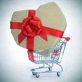 Heart-shaped gift in a shopping cart Royalty Free Stock Photos