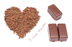 Heart shaped grated chocolate and three candies on white background Stock Photography