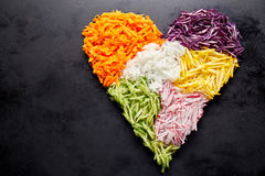 Heart shaped grated vegetables. Heart shaped pile of grated vegetables as ingredients for cooking placed over black surface background with copy space. Healthy Royalty Free Stock Images