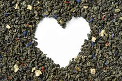Heart shaped of green tea with soursop, safflower petals and knapweed on white background. royalty free stock photo