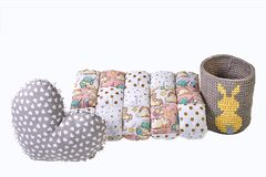 Heart shaped grey pillow, patchwork comforter and knitted basket with yellow rabbit on white background. Heart shaped grey pillow, patchwork comforter and Royalty Free Stock Image