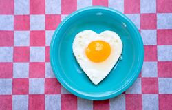 Heart-shaped grilled egg on a teal plate