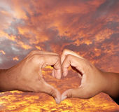 Heart shaped hand gesture 2. Close up photo of a African American male and female hands forming a heart shape to symbolize love and Valentines Day isolated via royalty free stock photos