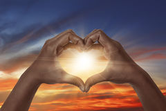 Heart shaped hand with sunrise. Background. heart shaped hand is a symbol of love, freedom, romance Stock Photography
