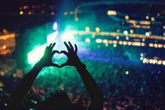 Heart shaped hands at concert, loving the artist and the festival. Music concert with lights and silhouette of a man enjoying. The concert