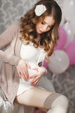 Heart shaped hands of pregnant woman on her belly Stock Photography