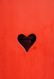 Heart shaped hole. Red wooden surface with heart shaped hole royalty free stock image
