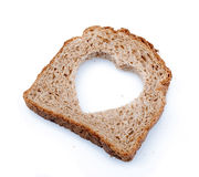 Heart shaped hole in a slice of bread Royalty Free Stock Image