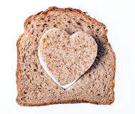 Heart shaped hole in a slice of bread Stock Images