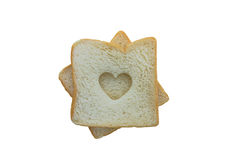 Heart shaped hole in a slice of bread isolated Royalty Free Stock Photos