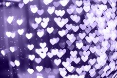 Heart shape blurred bokeh background with sparkles. Ultra violet. Heart shaped holiday blurred bokeh background with sparkles. Valentine background. Christmas Stock Photo