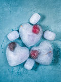 Heart shaped ice cubes with frozen cherry Stock Images