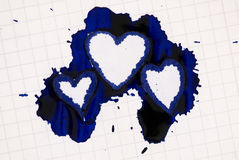 Heart shaped ink blot on paper. Three heart shaped blue ink blots on paper Stock Photo