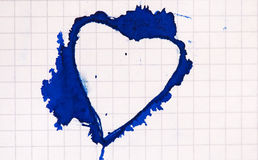 Heart shaped ink blot on paper. Heart shaped blue ink blot on paper Stock Image