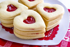 Heart shaped jam filled sugar cookies. Close up of stacks of linzer cookies heart shaped sitting on white heart plate with white and red heart napkin Stock Images