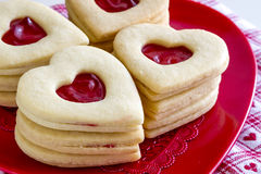 Heart shaped jam filled sugar cookies. Stacks of linzer cookies heart shaped sitting on red heart plate with white and red heart napkin Stock Photo