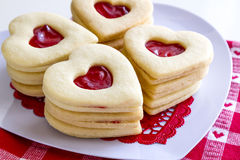 Heart shaped jam filled sugar cookies. Stacks of linzer cookies heart shaped sitting on white heart plate with white and red heart napkin Stock Photos