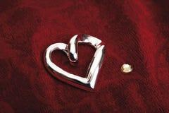 Heart shaped jewelery on red velvet Stock Images