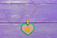 Heart shaped jewelry for Valentine`s Day. Valentines day felt heart jewelry  on the purple wooden background. Cute gift. Heart shaped jewelry. Valentines day Royalty Free Stock Photography