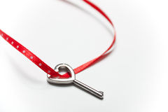 Heart shaped key and red ribbon Royalty Free Stock Photos