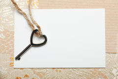 Heart shaped key on a white card. Royalty Free Stock Photography