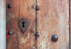 Heart shaped keyhole surround in old wooden door. Royalty Free Stock Photos